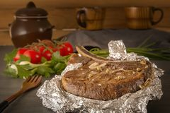 Meat steak baked in foil on a wooden table with fresh tomatoes and greens. Close-up royalty free stock photo