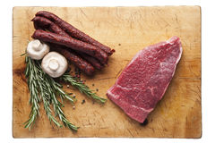 Meat steak on a cutting board with sausages. Wooden cutting board with beef steak and sausages, top view Royalty Free Stock Image
