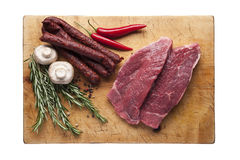 Meat steak on a cutting board with vegetables. Wooden cutting board with beef steak ans sausage and vegetables, top view Stock Images