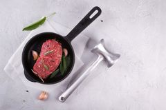 Meat steak on frying pan with ingredients for cooking on a gray concrete background with meat hammer Top view. stock image