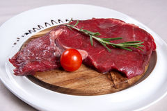 Meat for steak. Raw beef steak on a plate with a tomato and a sprig of greenery Royalty Free Stock Photo