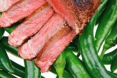 Meat steak sliced over green hot chili peppers Stock Photos