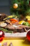 Meat steak with vegetables. spruce branches and Christmas balls on backdrop. Baking paper and wood board on yellow background. on meat is a piece of natural stock photo