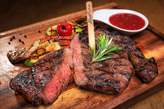 Meat steak on the wooden board. With sauce Stock Images