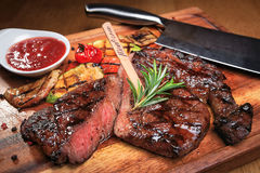 Meat steak on the wooden board with sauce stock images