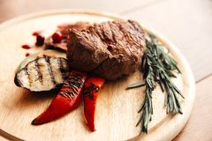Meat steak on a wooden plate with a side dish of grilled vegetables stock photo