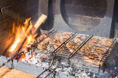 Meat steaks on grill and skewers at stone brazier with fire flames. Barbecue outdoor party concept stock photos