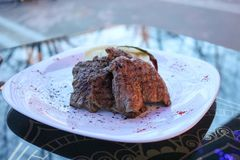 Meat steaks, pork, beef on a white plate on a table in a cafe, restaurant in the evening. Fried meat steaks, pork, beef on a white plate on a table in a cafe Stock Photo