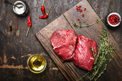 Meat steaks on rustic cutting board with thyme, oil and spices. Dark wooden background Stock Photos