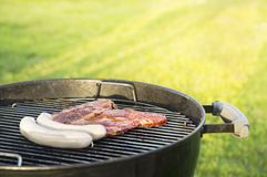 Meat steaks and sausages on grill Royalty Free Stock Photo