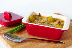 Meat stew with pickles in a ceramic stewpot. Meat stew with pickles. in red ceramic stewpot .stands on a cutting board.near spoon and cover saucepan.on white Stock Photos