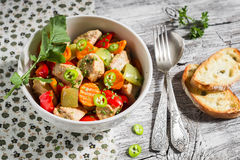 Meat stew with vegetables - carrots, onions and sweet peppers in a white bowl Royalty Free Stock Photo