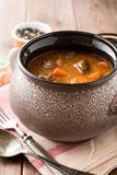 Meat stew with vegetables in ceramic pot on wooden table. Selective focus Stock Image