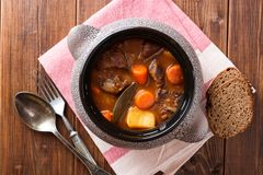 Meat stew with vegetables in ceramic pot on wooden table. Top view Royalty Free Stock Photos