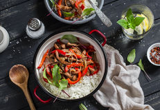 Meat stir fry with red peppers and rice in a pot, homemade lemonade with lemon on a dark wooden background. Delicious healthy lunc Royalty Free Stock Photos