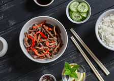 Meat stir fry with sweet red pepper, steamed rice and fresh cucumber and sesame salad Stock Photography