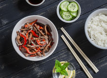 Meat stir fry with sweet red pepper, steamed rice and fresh cucumber and sesame salad Stock Photo