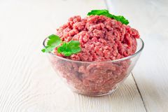 Fresh raw minced beef in a plate close up on a rustic wooden tab. Meat stuffing for cutlets or meatballs in a glass bowl on a white table. The concept: food Royalty Free Stock Images