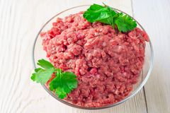 Raw minced meat in a plate on white background - top view. Meat stuffing for cutlets or meatballs in a glass bowl on a white table. The concept: food, cooking Stock Photos