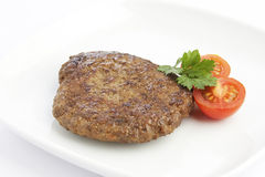 Meat with tomatos and herbs. Escalope with tomatoes and herbs on white plate Royalty Free Stock Photography