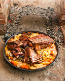 Meat under a bell. Three different types of meat (lamb, pork and veal) prepared on a special, traditional way - under the bell covered with live coals Royalty Free Stock Image