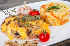 Meat under cheese and mushrooms with rice Stock Photos