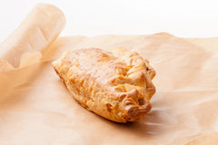 Meat and Vegetable Pasty. Homemade meat and vegetable pasty with flaky pastry on a brown paper background Royalty Free Stock Photography