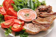 Meat and vegetables. Fried pork with cut vegetables on a big plate Royalty Free Stock Image