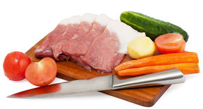 Meat and vegetables. Unprepared meat and vegetables on a cutting board Royalty Free Stock Photos