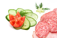 Meat and vegetables. Sliced ham and sausage, cucumber and tomato with a sprig of dill Royalty Free Stock Photos