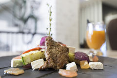 Meat with vegetables and cheese in restaurant Stock Photography