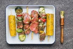 Meat, vegetables and corn Skewers in  green herbs rubs and Marinades with Brush Stock Photo