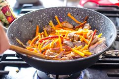 Meat with vegetables in frying pan wok on stove stock photo