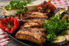 The meat and vegetables roasted on a grill with fresh greens black plate in style rustic Stock Photo