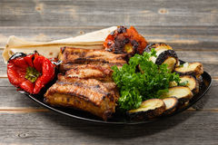 The meat and vegetables roasted on a grill with greens   black plate in style  rustic Royalty Free Stock Photography