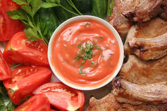 Meat and vegetables with sauce. Fried pork with cut vegetables on a big plate Stock Image