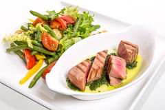 Meat with vegetables. Serving meat with vegetables on white background Stock Photography