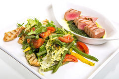 Meat with vegetables. Serving meat with vegetables on white background Stock Images
