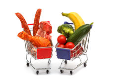 Meat and vegetables in two shopping carts, isolated on white Royalty Free Stock Photography