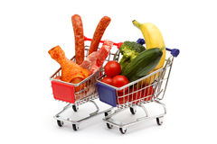 Meat and vegetables in two shopping carts, isolated on white Royalty Free Stock Images