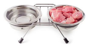 Meat and water for pets in metal bowls isolated Royalty Free Stock Photography
