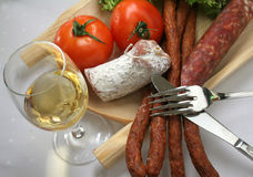 Meat and wine. Pork sausage with fresh tomato and glass of wine Stock Photos