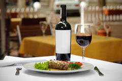 Meat and wine served. Selective focus on meat, clear white label at bottle Royalty Free Stock Images