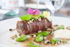 Meat wrapped in Prosciutto. Served with green beans and topped with edible flowers Stock Photos