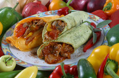 Meat wraps and vegetables. Elk meat and vegetables in a tortilla wrap, surrounded by fresh vegetables royalty free stock photo