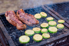 Meat and zuccini slices on grill Stock Image