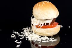 Meatball in a bun with tomato mayonnaise and grated cheese on the black background Royalty Free Stock Photo