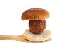 Meatball on a bun on a wooden spoon Royalty Free Stock Photos