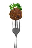 Meatball on fork. Meatball with herbs on a fork isolated over white Royalty Free Stock Photos