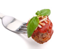 Meatball with sauce, cheese and basil on a fork Royalty Free Stock Photo